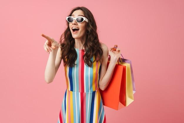 Retrato de uma bela jovem chocada e surpresa positiva posando isolada sobre uma parede rosa, segurando sacolas de compras apontando para o lado