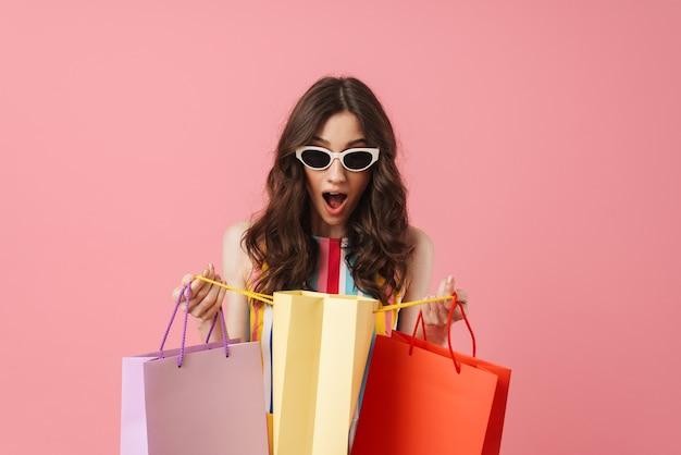 Retrato de uma bela jovem chocada e surpresa positiva posando isolada sobre uma parede rosa, segurando sacolas de compras