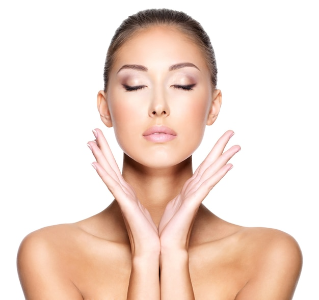 Retrato de uma bela jovem com pele clara e saudável que quer tocar seu rosto com as duas mãos
