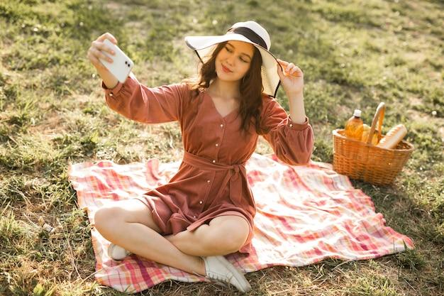 Retrato de uma bela jovem com um chapéu e um telefone celular
