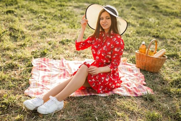 Retrato de uma bela jovem com um chapéu no verão no parque