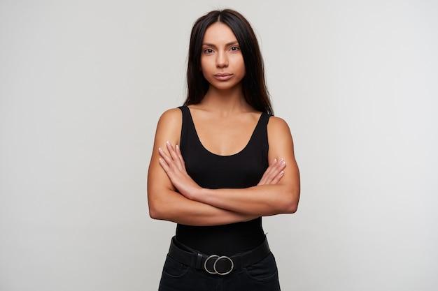 Retrato de uma bela jovem de cabelos escuros com maquiagem casual, cruzando as mãos sobre o peito enquanto olha calmamente, vestida com roupas pretas em pé no branco