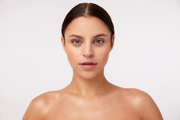 Retrato de uma bela jovem de cabelos escuros com olhos verdes usando maquiagem natural e parecendo calma, em pé com ombros nus