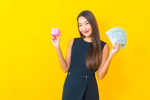 Retrato de uma bela jovem de negócios asiáticos com muito dinheiro e dinheiro em fundo amarelo.