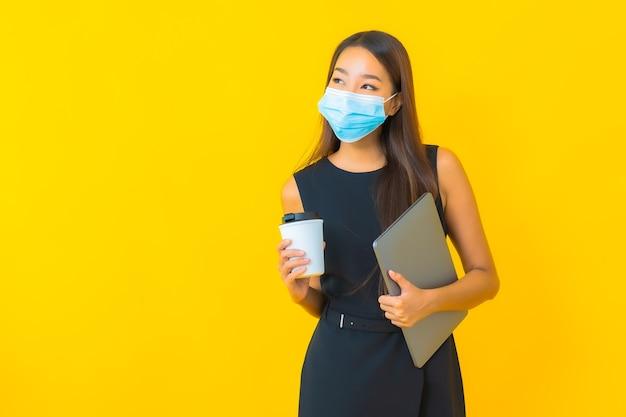 Retrato de uma bela jovem de negócios asiáticos usando máscara para proteger covid19 com um computador laptop