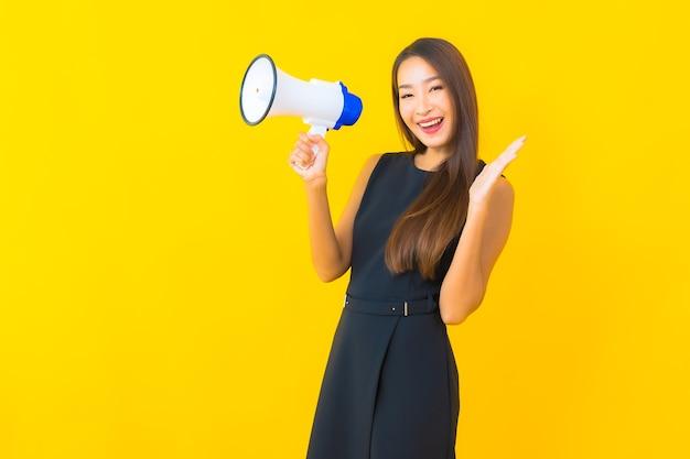 Retrato de uma bela jovem de negócios asiáticos usando megafone para comunicação
