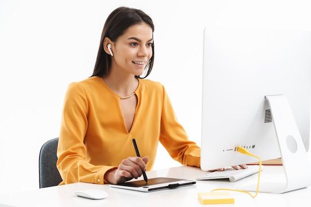 Retrato de uma bela jovem designer usando computador tablet gráfico e caneta stylus enquanto trabalhava em um escritório luminoso