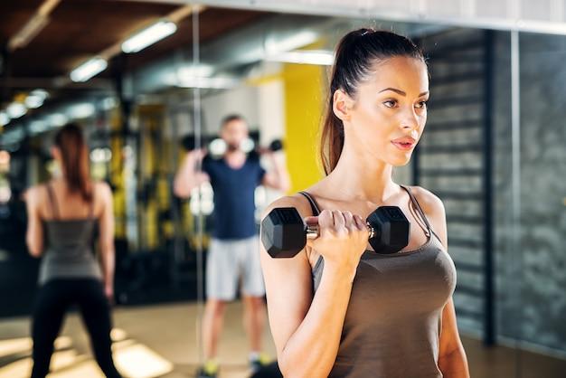 Retrato de uma bela jovem desportiva focada em um ginásio, segurando o peso em uma mão,