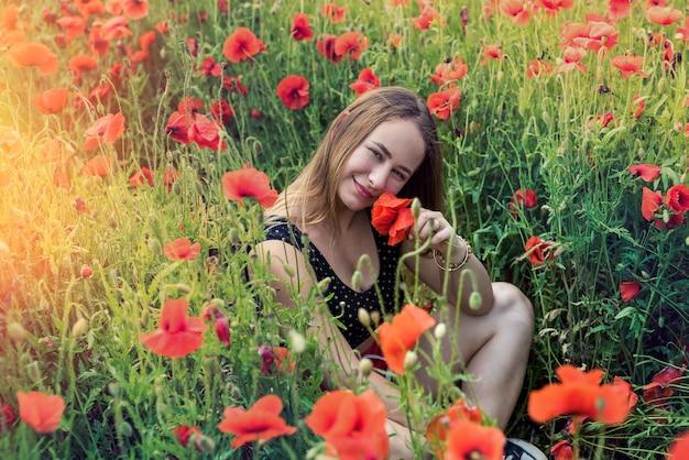 Retrato de uma bela jovem em roupas esportivas, sentado no campo de papoulas florescendo. desfrute da liberdade no dia de verão