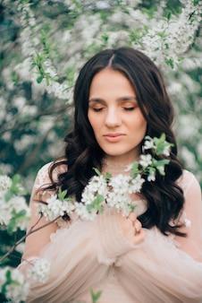 Retrato de uma bela jovem em um vestido leve na superfície de um jardim florido