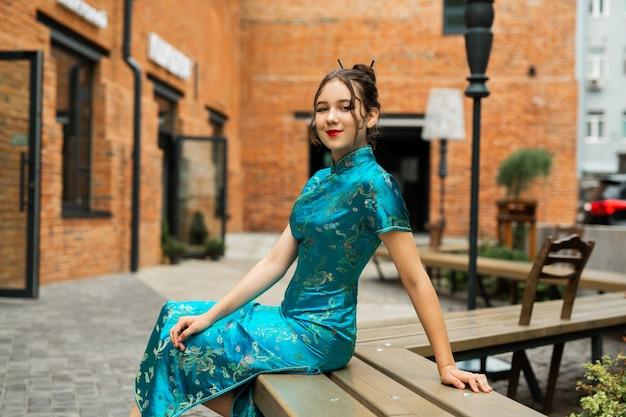 Retrato de uma bela jovem em um vestido tradicional sentado em um banco