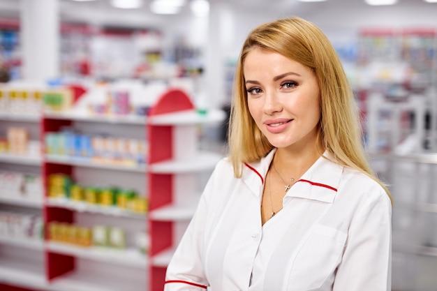 Retrato de uma bela jovem farmacêutica de uniforme na drogaria moderna