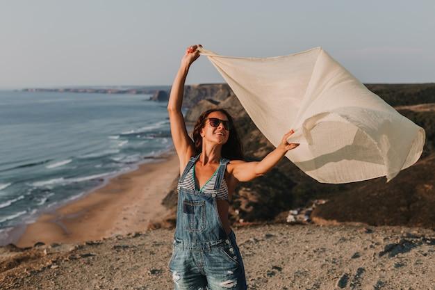 Retrato de uma bela jovem feliz jogando com um lenço e o vento no topo de uma colina. horário de verão. estilo de vida