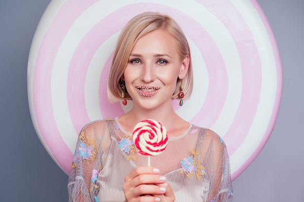 Retrato de uma bela jovem loira, barbie sexy feminino confeitaria polvilhando açúcar colorido nos lábios confeiteiro maquiagem perfeita segurar pirulito dieta doces falsos doces fundo em estúdio tiro.