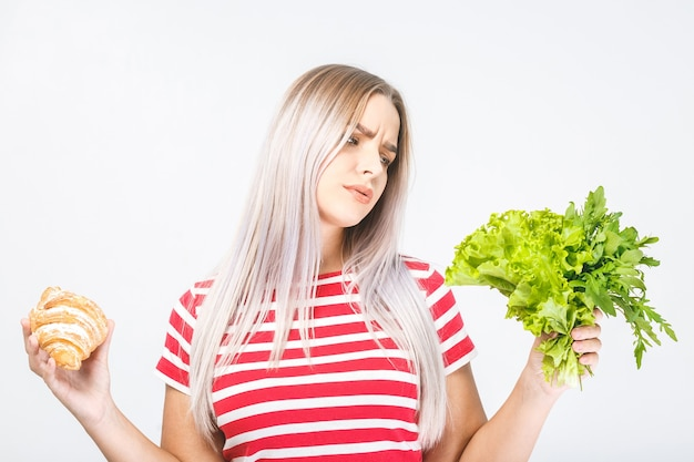 Retrato de uma bela jovem loira confusa, escolhendo entre uma comida saudável e uma alimentação pouco saudável. isolado sobre fundo branco.