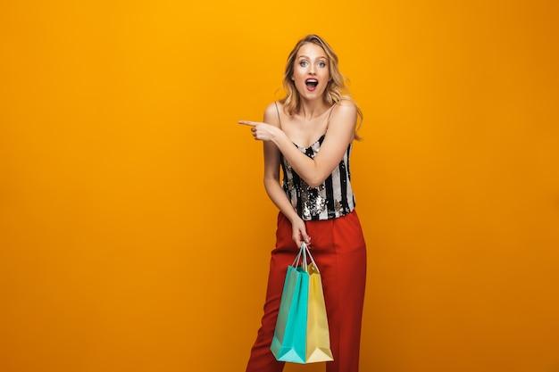 Retrato de uma bela jovem loira em pé isolado sobre um fundo amarelo, carregando sacolas de compras, apontando para longe