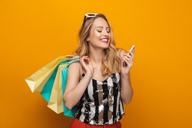 Retrato de uma bela jovem loira em pé isolado sobre um fundo amarelo, usando telefone celular
