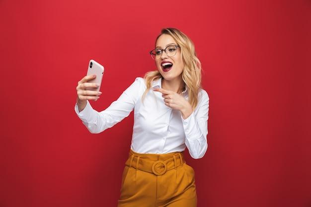 Retrato de uma bela jovem loira em pé isolado sobre um fundo vermelho, tirando uma selfie e apontando o dedo