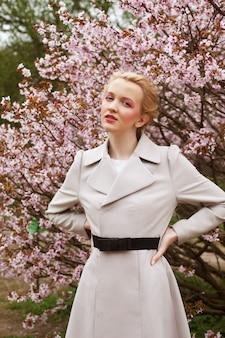 Retrato de uma bela jovem loira em um fundo de flores de cerejeira rosa na primavera