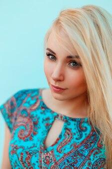 Retrato de uma bela jovem loira em um vestido azul com padrões perto de uma parede azul brilhante