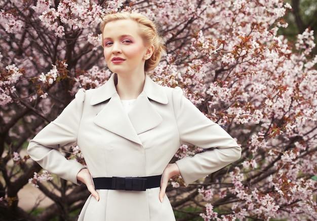 Retrato de uma bela jovem loira em uma de flores de cerejeira rosa na primavera