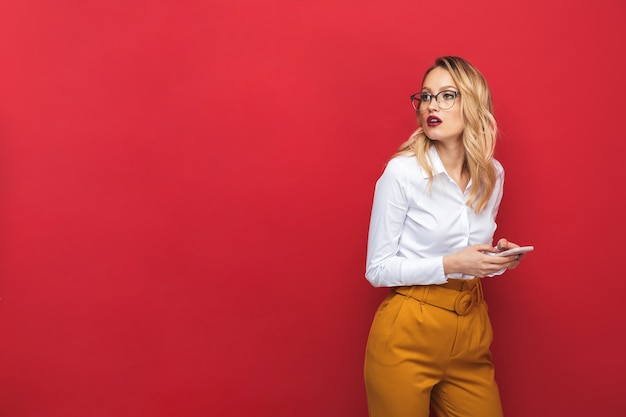 Retrato de uma bela jovem loira pensativa de pé isolado sobre um fundo vermelho, segurando um telefone celular