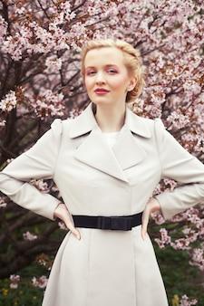 Retrato de uma bela jovem loira por flores de cerejeira na primavera