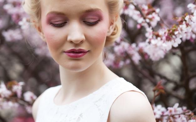 Retrato de uma bela jovem loira por flores de cerejeira rosa na primavera