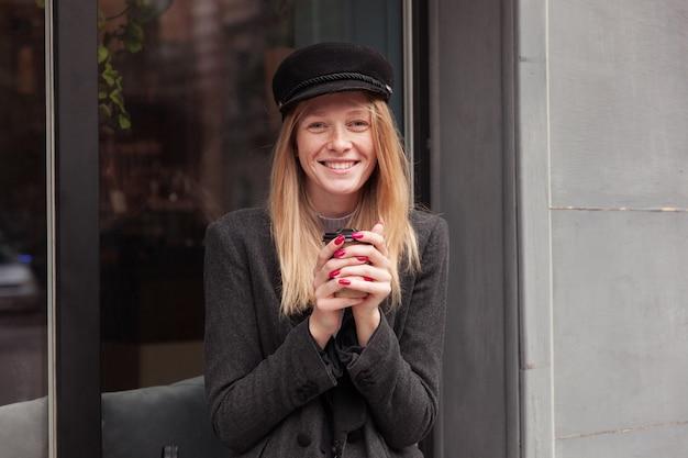 Retrato de uma bela jovem loira positiva com chapéu preto, segurando uma xícara de café nas mãos levantadas e olhando alegremente com um sorriso encantador, posando ao ar livre com roupas cinza elegantes