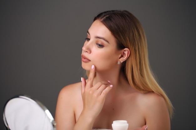 Retrato de uma bela jovem loira usando cosméticos para a pele