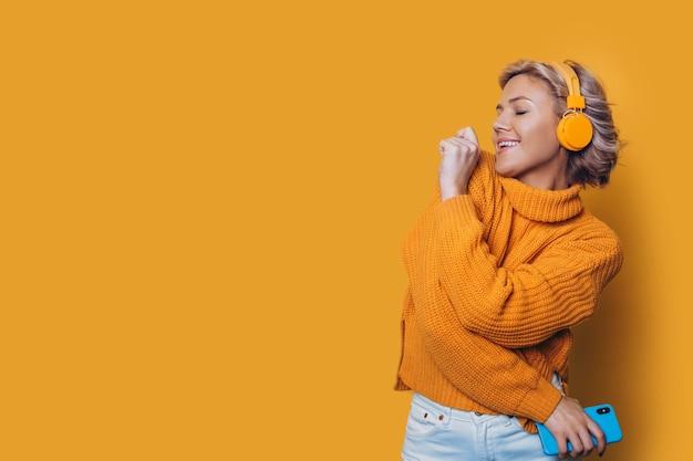 Retrato de uma bela jovem loira vestida de amarelo dançando isolada na parede amarela, ouvindo meditando com fones de ouvido amarelos.