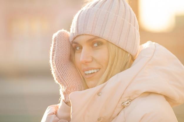 Retrato de uma bela jovem modelo de chapéu de malha rosa e luvas. natural linda jovem loira sorridente usando luvas de malha