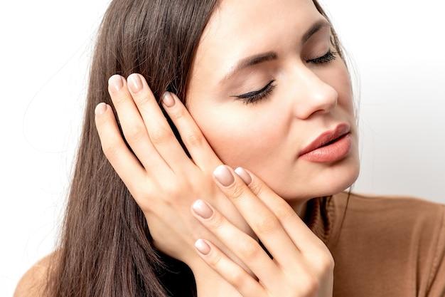 Retrato de uma bela jovem morena de olhos fechados, tocando seu cabelo com dedos bem cuidados
