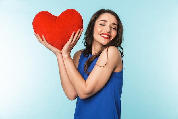 Retrato de uma bela jovem morena de pé sobre o azul, segurando um coração vermelho