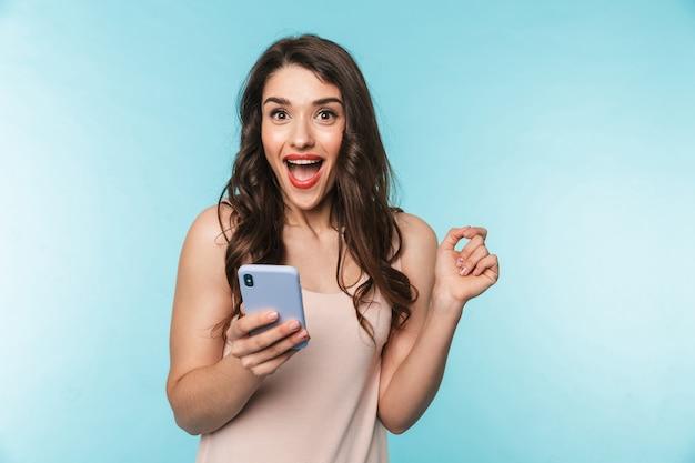 Retrato de uma bela jovem morena de pé sobre o azul, usando telefone celular, comemorando