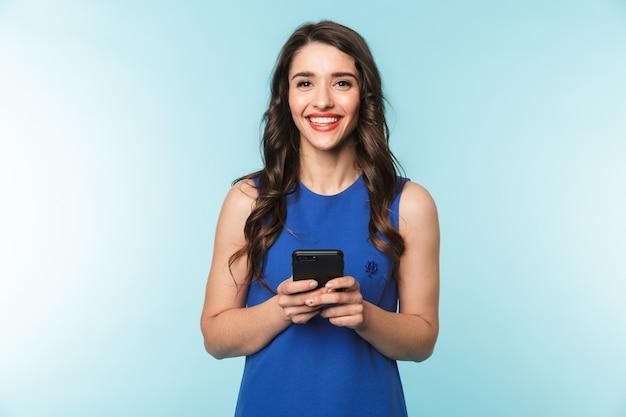Retrato de uma bela jovem morena de pé sobre o azul, usando um telefone celular