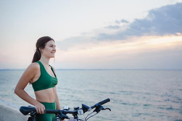 Retrato de uma bela jovem morena descansando após passeio de bicicleta ao nascer do sol. modelo ouvindo música com fones de ouvido sem fio pela manhã.