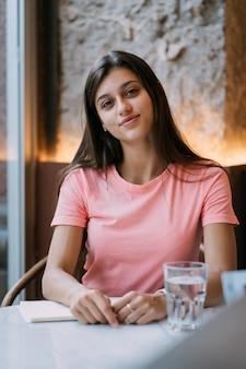Retrato de uma bela jovem morena em um café