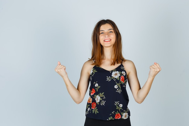 Retrato de uma bela jovem mostrando gesto de vencedor na blusa