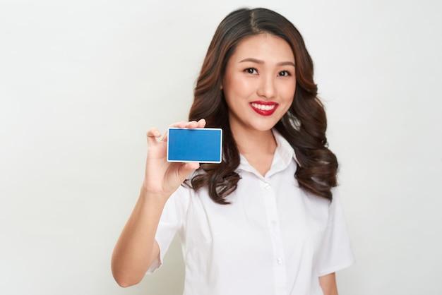 Retrato de uma bela jovem mostrando um cartão de crédito em branco