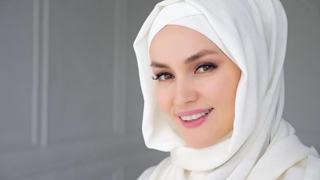Retrato de uma bela jovem muçulmana árabe usando hijab branco, levantando lentamente os olhos, olhando para a câmera e sorrindo.