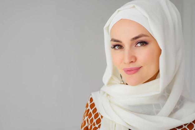 Retrato de uma bela jovem muçulmana árabe usando hijab branco, olhando para a câmera, copie o espaço