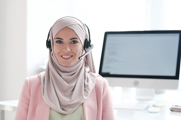 Retrato de uma bela jovem muçulmana positiva em hijab respondendo a perguntas usando o dispositivo viva-voz em uma central de atendimento