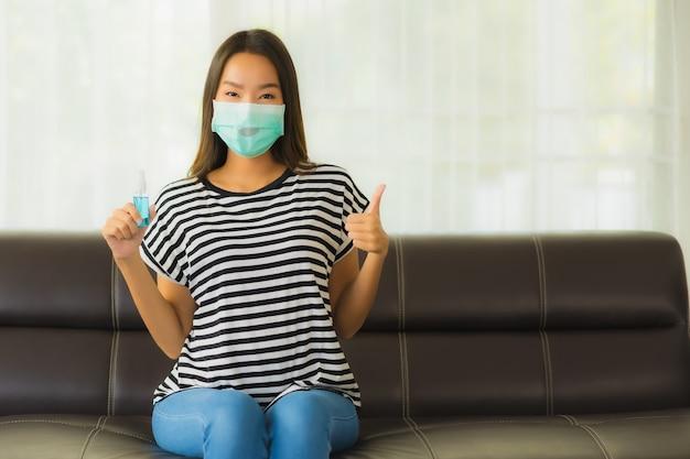 Retrato de uma bela jovem mulher asiática com máscara no sofá