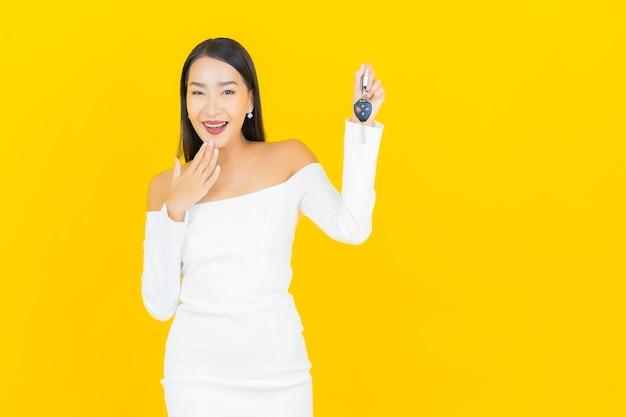 Retrato de uma bela jovem mulher asiática de negócios com a chave do carro na parede amarela