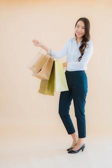 Retrato de uma bela jovem mulher asiática de negócios com muitas sacolas de compras no varejo e em loja de departamentos