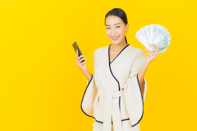 Retrato de uma bela jovem mulher asiática de negócios com muito dinheiro e cofrinho na parede amarela
