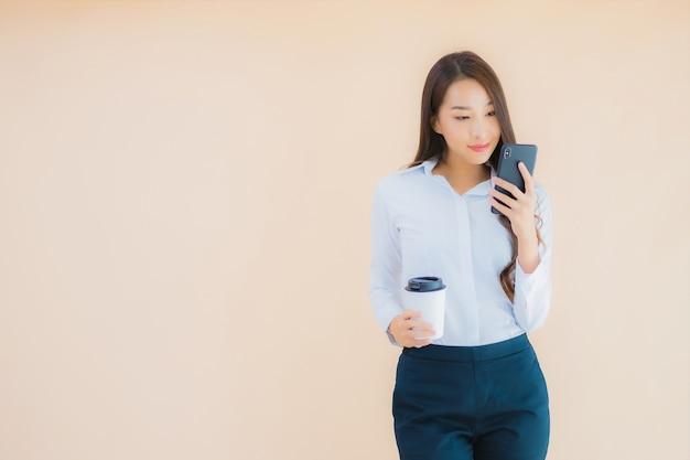Retrato de uma bela jovem mulher asiática de negócios com telefone celular inteligente e xícara de café