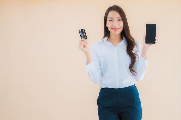 Retrato de uma bela jovem mulher asiática de negócios com telefone e cartão de crédito