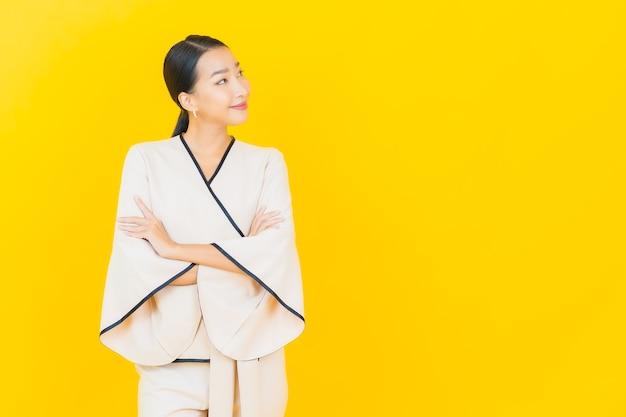 Retrato de uma bela jovem mulher asiática de negócios sorrindo com um terno branco na parede amarela